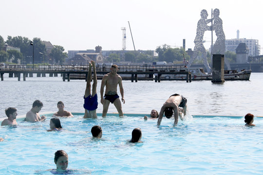 People swim in a floating swimming pool anchored on the bank of Spree river in Berlin