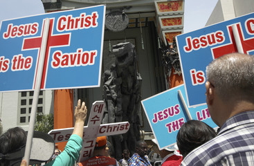 A parade of evangelical Christians chant religious slogans near a statue of movie monster Godzilla in front of the TCL Chinese Theatre IMAX forecourt in California