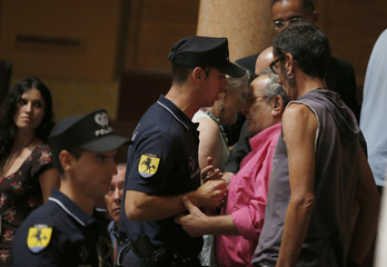 Police officials expel members of the public after they wore red clown noses during the debate to vote on a motion of confidence in Lisbon