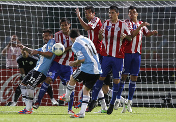 Argentina's Lionel Messi (back to camera) takes a free kick during their World Cup 2014 qualifying soccer match against Paraguay in Cordoba