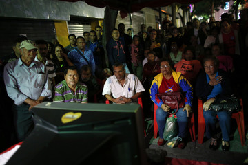 Supporters of Venezuelan President Hugo Chavez watch a government national TV broadcast with news about the president's health in Caracas