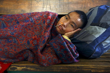 A sick woman waits for a bus at a bus station to head back for her village after an earthquake in Kathmandu