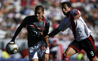River Plate's Rogelio Funes Mori fights for the ball with Estudiandes de La Plata's German Re during their Argentine First Division soccer match in Buenos Aires