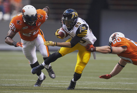 Hamilton Tiger-Cats wide receiver Williams is chased by BC Lions defensive back Reddick  and linebacker Bighill during CFL football game in Vancouver