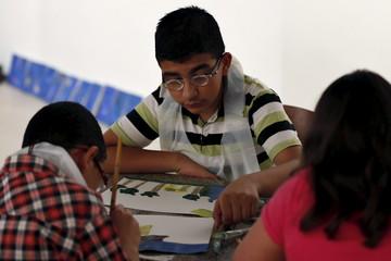 Qouqaz paints at an art exhibition in Amman