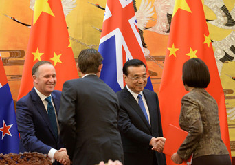 China's Premier Li Keqiang attends a signing ceremony with New Zealand's PM John Key after their meeting at the Great Hall of the People in Beijing
