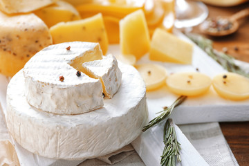 Beautiful composition with variety of cheese on wooden board