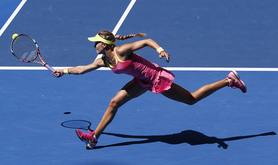 Bouchard of Canada hits a return to Begu of Romania during their women's singles match at the Australian Open 2015 tennis tournament in Melbourne
