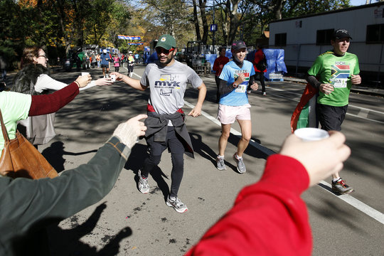 Runners participating in fun runs are handed water by a group of friends who created their own aid station in Central Park