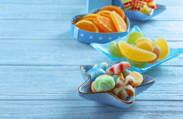 Composition with tasty jelly candies on wooden background