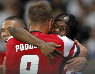 Arsenal's Gervinho celebrates with teammate Podolski after scoring the second goal for his team during their Champions League soccer match against Montpellier at the Stade de la Mosson stadium in Montpellier