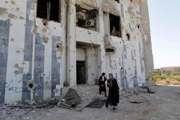 Libyans visit the destroyed headquarters of Benghazi University, in Benghazi
