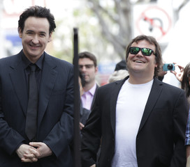 Cusack smiles next to actor Jack Black before unveiling his star on the Walk of Fame in Hollywood
