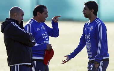 Paraguay's head coach Diaz talks to his son and assistant coach Emiliano during a training session in La Serena