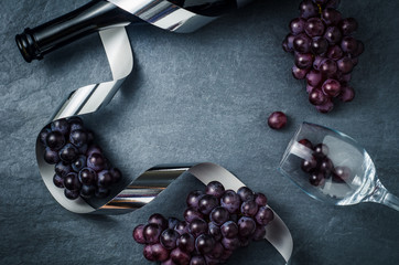 Wineglass , bottle with ripe grapes and ribbon on black stone background.