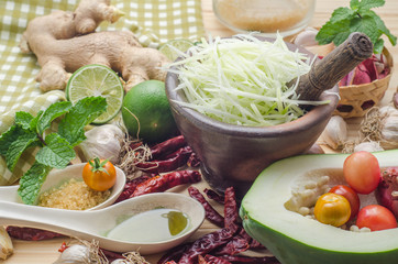 Ingredients for making papaya salad on a wooden table. Set of Thai spices and herbs