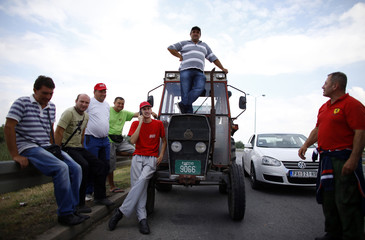 Farmers stand as they partially block a road with tractors during a protest in the Serbian town of Pancevo