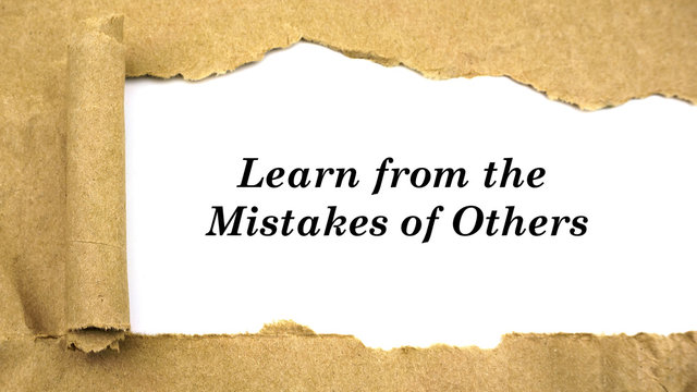 "Torn paper with word ""learn from the mistakes of others"""