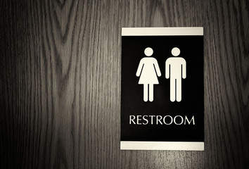 horizontal black and white image of a unisex bathroom sign for men and woman together