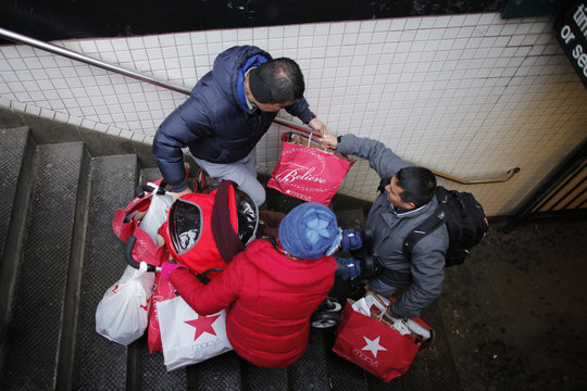 Shoppers go down the stairs with some bags and a stroller after their making purchases in New York
