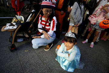A girl in costume waits for a Halloween parade to start in Kawasaki