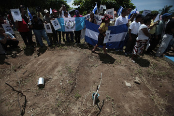 """Central American immigrant members of the """"Caravana Paso a Paso Hacia la Paz"""" (Caravan Step by Step to Peace), protest in cemetery in Arriaga"""