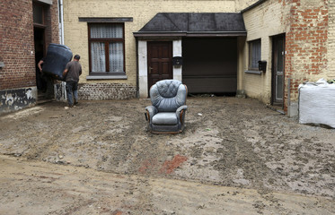 Residents remove an armchair from a flooded house after heavy rains hit the town of Ittre