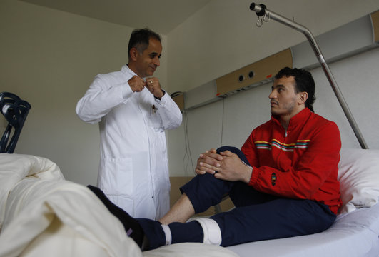 Syrian heavyweight boxer Nasser Al Shami speaks to his doctor at the Marien-hospital, where he is receiving treatment for his leg, in Witten