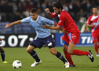 Lazio's Klose challenges Catania's Spolli during their Italian Serie A soccer match at the Olympic stadium in Rome