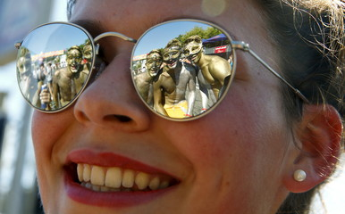 Posing revellers are reflected in the sunglasses of a woman during the 24th Street Parade dance music event in Zurich