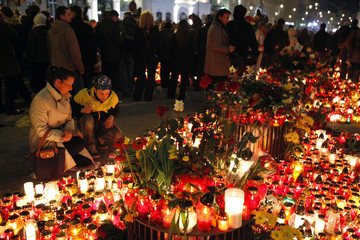 People gather in front of the Presidential Palace in Warsaw to pay their respects to the late Polish President Kaczynski and his wife Maria