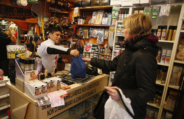 Shoemaker Arellano deals with a customer as he works in his shop in downtown Rome