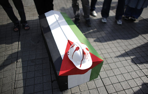 A mock coffin and hard hat, representing what protesters said were Palestinian engineers and architects who killed by Israeli troops, are placed on the ground during a pro-Palestinian demonstration in Istanbul