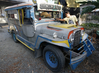 Erly Famadula cleans a jeepney bought from remittances sent by his wife Susan, in the town of Santa Maria