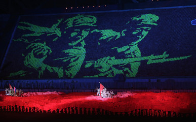North Koreans students use different coloured cardboards to form a picture of soldiers as background in Pyongyang
