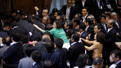 Japan's PM Abe sits next to Defense Minister Nakatani as he looks at lawmakers crowding around Konoike, chairman of the upper house special committee on security, during a vote at the parliament in Tokyo