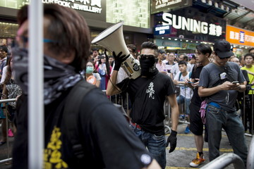 A masked localist protester carries a bullhorn during an anti-China protest at Mongkok shopping district in Hong Kong, China