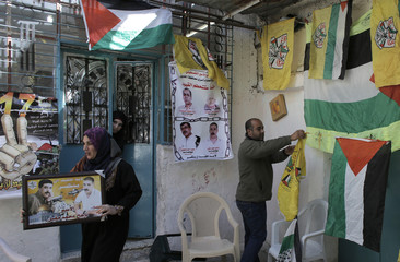 Relatives of Palestinian prisoner Muqbel hang flags and pictures as they prepare for his release in al-Aroub refugee camp near the West Bank city of Hebron