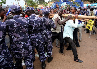 Opposition supporters walk in front of policemen in Kampala