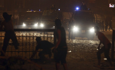 Protesters throw stones towards riot police during clashes along a road at Kornish El Nile which leads to the U.S. embassy, near Tahrir Square in Cairo