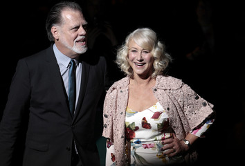 British actress Helen Mirren poses with her husband Taylor Hackford for photographers on the catwalk before Dolce & Gabbana 2012 Autumn/Winter collection during Milan Fashion Week
