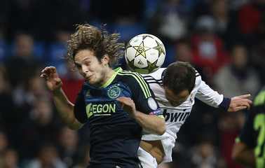Real Madrid's Ricardo Carvalho fights to head the ball with Ajax Amsterdam's Blind during their Champions League Group D soccer match at the Santiago Bernabeu stadium in Madrid