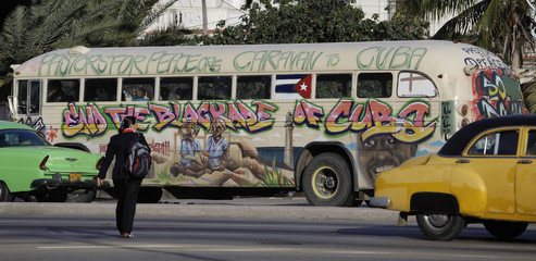 "A woman crosses a street as a bus of the U.S. based group ""Pastors For Peace"" passes by in Havana"