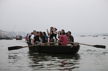 Tourist take pictures from a boat as people bath in the Ganges river in Varanasi