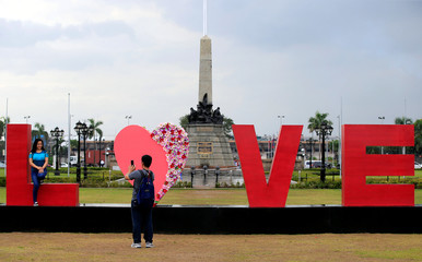 "People take pictures of a ""LOVE"" display day before Valentine's Day in Rizal park, metro Manila"