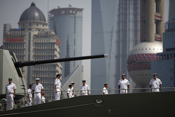 Crew members of the Australian HMAS Ballarat, ANZAC-class Guided Missile Frigate, stand at attention on the deck as they arrive at a port area of Huangpu River in Shanghai
