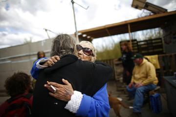 "Tracy ""Magenta"" Moss hugs Frank, who runs the internet cafe, in Slab City just outside Niland, California"