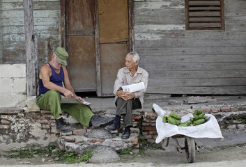 Two farmers read newspapers beside bananas for sale on the outskirts of Havana