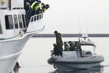 Greek Coast Guard officers in a speedboat approach activistshanging from the anchor's chain of a Turkish-flagged passenger boat carrying migrants to be returned to Turkey in an attempt to prevent it from leaving the port of Mytilene, on island of Lesbos