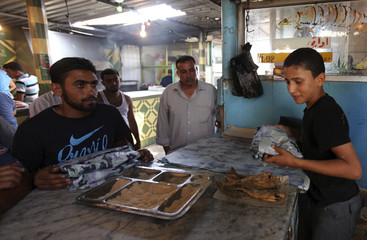 A youth sells cooked fish in a market in the Geleana area of Benghazi J